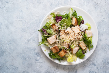 Caesar salad in white plate top view.