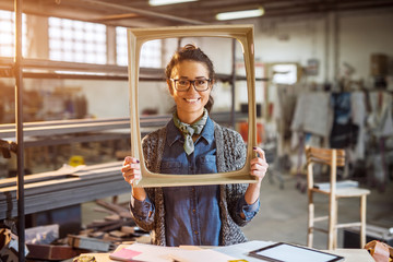 Excited middle-aged engineer holding old fashion picture frame in sunny fabric workshop and posing behind.