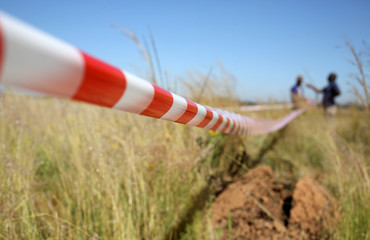Man gestures as he uses tape to mark vacant land in Olievenhoutbosch near Centurion