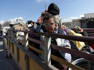 A child rides on the back of a truck in the town of Inab