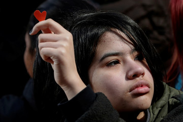 A student from Fiorello H. Laguardia High School holds a small red paper heart during the National School Walkout in the Manhattan borough of New York City