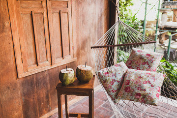 Hammock with colorful pillows and wooden table with two fresh coconuts. Wooden house