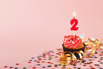 Second birthday cupcake with candle and sprinkles