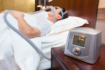 CPAP machine sitting on a bedside table with blurred Middle age asian man sleeping in his bed wearing CPAP mask in the background