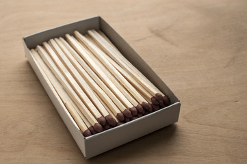Long wooden safety matchsticks stacked in cardboard matchbox on wooden background