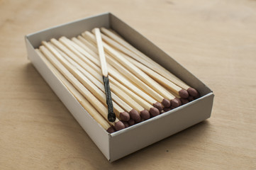 Long wooden safety matchsticks and one burnt matchstick stacked in cardboard matchbox on wooden background