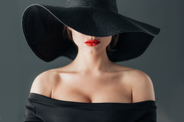 woman in black hat with red lips, on gray background, selective focus. Elegance and feminine sensuality