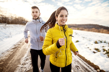 Close up of two sportive active fitness friends running on a winter day in the nature covered in snow.