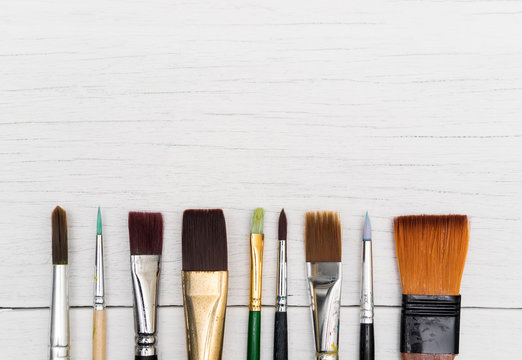 Watercolor brushes set on white wood background.
