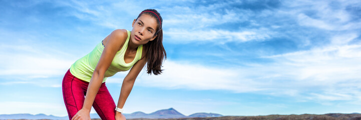 Exercise tired runner girl taking a break breathing during jogging training workout outdoor on desert trail. Asian woman sweating in summer heat. banner panoramic header with copy space on sky.