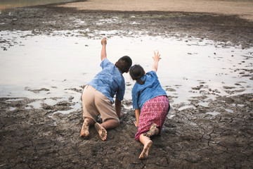 Sad boy and girl praying for the rain on lake, Concept drought and shortage of water crisis