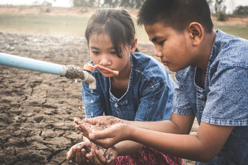 Sad children want to drink some water on crack ground , Concept drought and shortage of water crisis