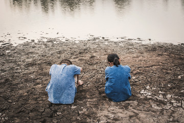 Sad boy and girl sitting on cracked dry ground, Concept drought and shortage of water crisis
