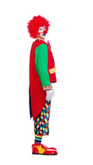 Side view full length picture of a clown in a white studio