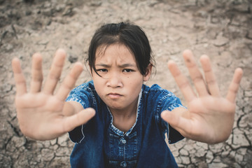 Sad girl on cracked dry ground , Concept drought and shortage of water crisis, selective and soft focus