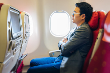 Young asian businessman with suits sitting on seat in airplane near the window and sleeping with relaxing