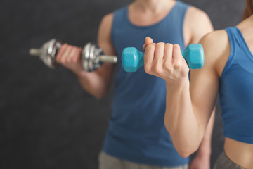 Fitness couple making exercise with dumbbells