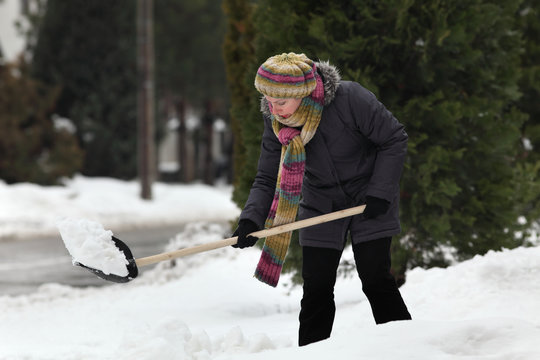 Caucasian woman cleaning snow from sidewalk using shovel, winter time at street