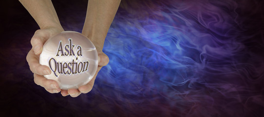 Crystal Ball showing Ask a Question  -  pair of hands holding a large crystal ball showing ASK A QUESTION on gaseous wispy black and blue background with  copy space on right side