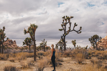 Woman at Joshua Tree with cloudy sky