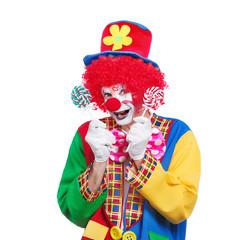 Happy clown in a hat holding lollipop sweets