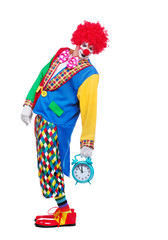 Full length side view picture of a clown holding alarm clock in a hand behind him