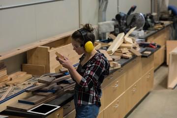Female carpenter examining a piece of wood
