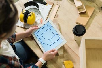 Female carpenter looking at plan on digital tablet