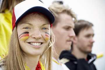 German football supporter smiling at match, portrait