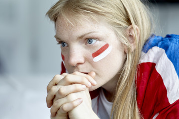 Sports enthusiast watching match with hands clasped in front of mouth