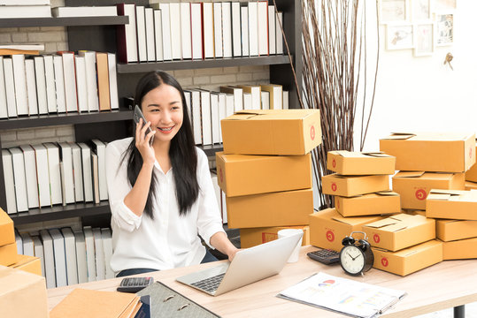 Asian business woman selling online marketing, shipping concept, startup small business working with computer at workplace. seller check product order and inventory, packing for delivery to customer.