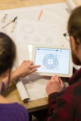 Male and female carpenters looking at plan on digital tablet