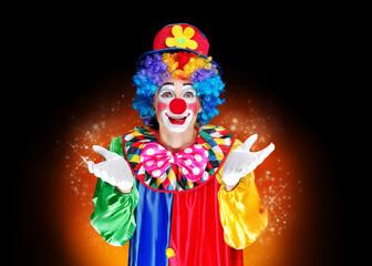 Clown in a magic glow against black background