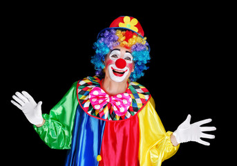 Happy clown with spread hands isolated on black background
