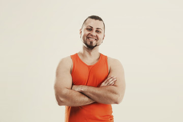 portrait of a sporty guy - bodybuilder in jeans and orange t-shirt