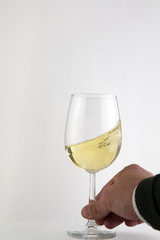 Hand with a White Wine Glass in Motion