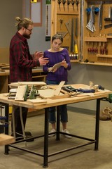 Male and female carpenters discussing over digital tablet