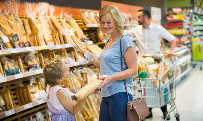 Customers in bread section in food store.