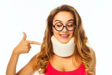 Young beautiful woman in round funny glasses wearing medical collar and pointing on it over white background