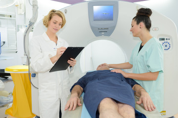patient lying on mri machine while female doctor and nurse
