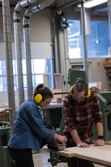Female carpenter using jack plane while male looking at her