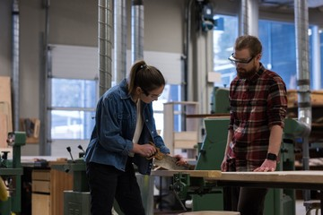 Female carpenter using hand saw while male looking at her