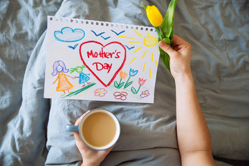 young mother get surprise present for mother day in bed. woman hold picture of her child for mother day