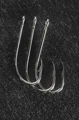 Fishing equipment: Three fishing hooks on a dark background.