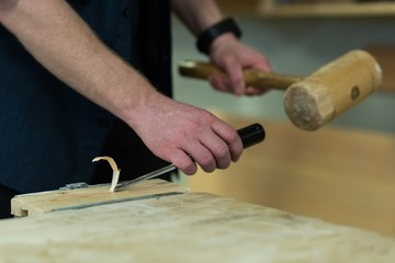 Male carpenter using chisel with hammer on a piece of wood