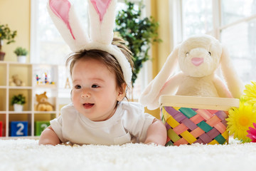 Baby boy with a stuffed rabbit celebrating Easter