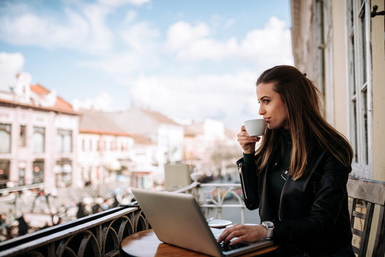 Woman drinking coffee on the terrace wihle working on a laptop.