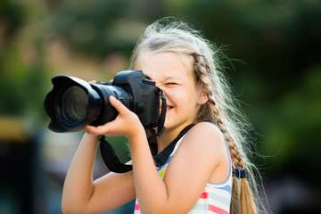 happy female child taking pictures with camera in park