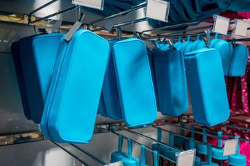 Many rows of blue pencil boxes hanging on metal rack in store.