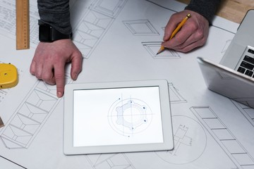 Male carpenter drawing a chart on chart paper